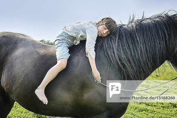 Cropped shot of boy leaning forward with eyes closed on horse in field