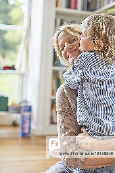Mutter und Sohn umarmen sich  lächeln