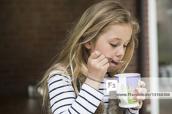 Girl spooning drink from mug