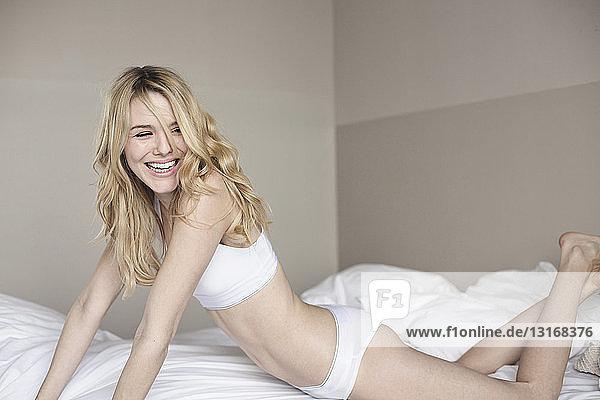 Junge Frau in Unterwäsche  die sich auf dem Bett nach vorne lehnt