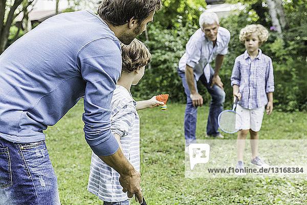 Reifer Mann und Sohn unterrichten Enkel Badminton im Garten