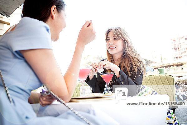 Junge Frauen sitzen am Tisch im Außenrestaurant
