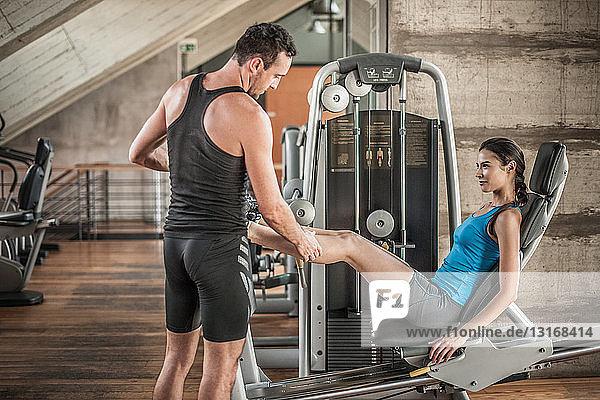 Persönlicher Trainer mit Frau mit Gewichtsausrüstung