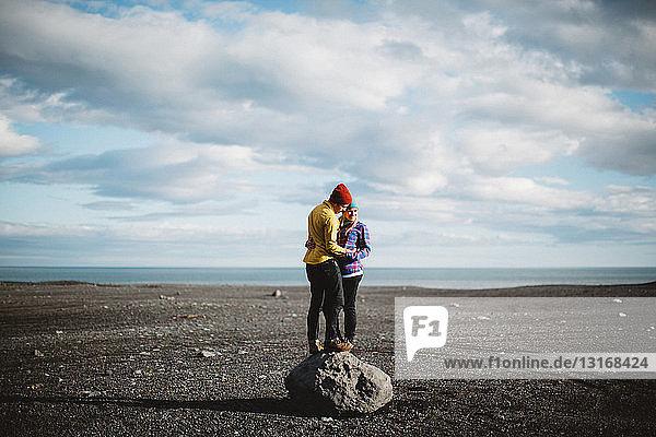 Mittelgroßes erwachsenes Paar auf einem Felsblock stehend  von Angesicht zu Angesicht in vulkanischer Landschaft umarmt  Island