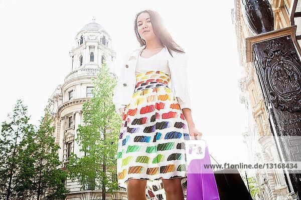 Junge Frau steht in Londoner Straße und trägt Einkaufstaschen