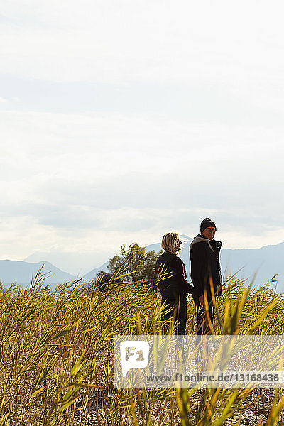 Reifere Paare  die Hand in Hand im Freien spazieren