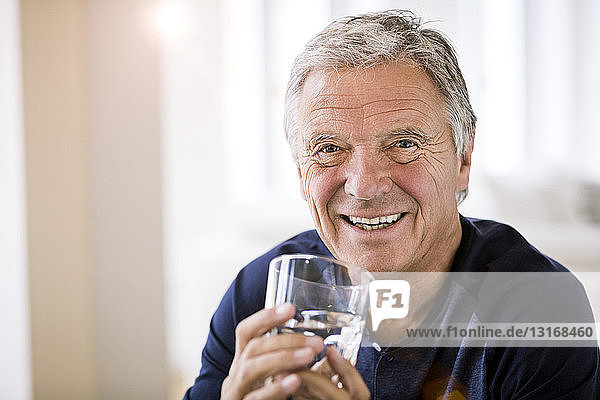 Portrait of senior man holding tumbler of water looking at camera smiling