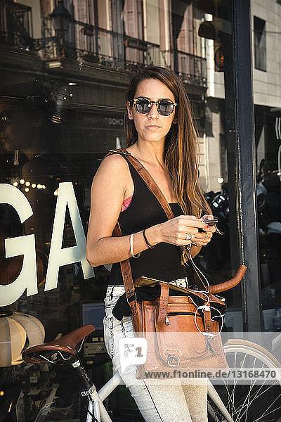 Woman using smartphone outside shop  Barrio Gotico  Barcelona  Spain