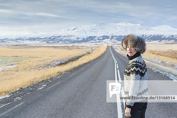 Reife Frau steht mitten auf der Landstraße  Island