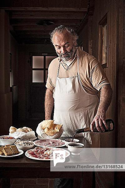 Mann legt Fleisch  Brot und Soße aus