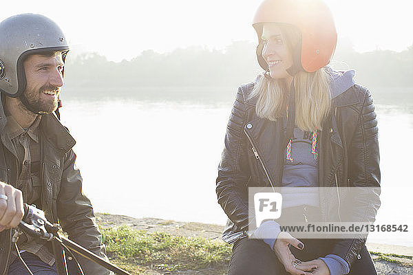 Mann sitzt auf Moped  spricht mit junger Frau  lächelt