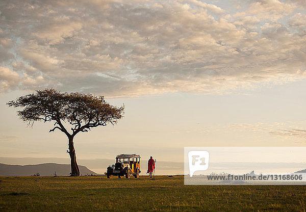 A Maasai man with an old replica safari vehicle near Cottars 1920s Camp in Cottars Conservancy  Kenya