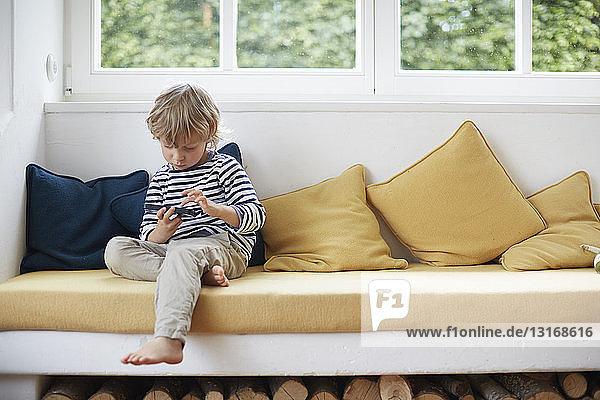 Junge sitzt auf einem Fenstersitz mit einem Smartphone und schaut nach unten