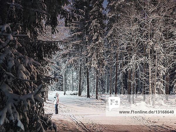 Mid adult woman standing on pathway in snowy forest  at night  Lahti  Finland