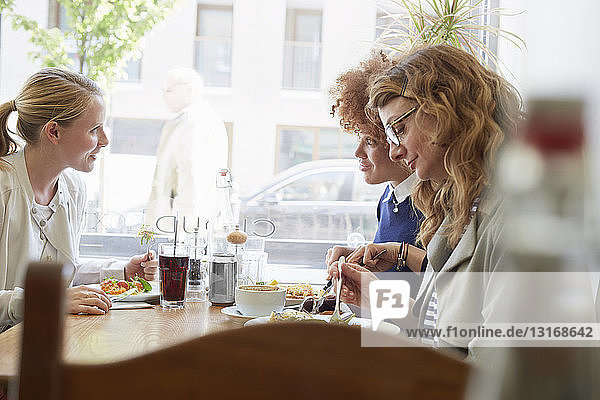 Three female friends eating lunch in cafe