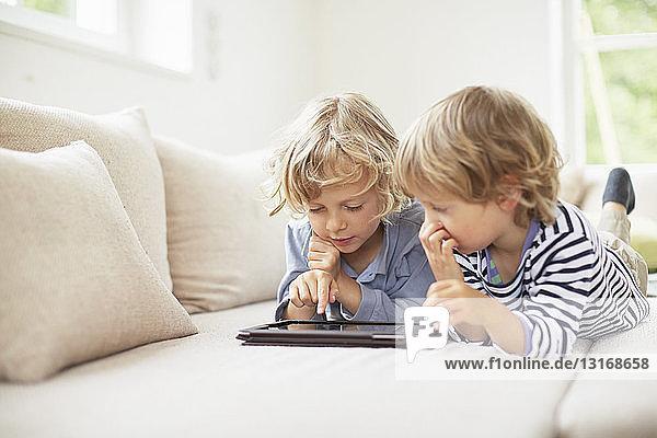 Zwei Jungen liegen vorne nebeneinander auf dem Sofa und benutzen ein digitales Tablett