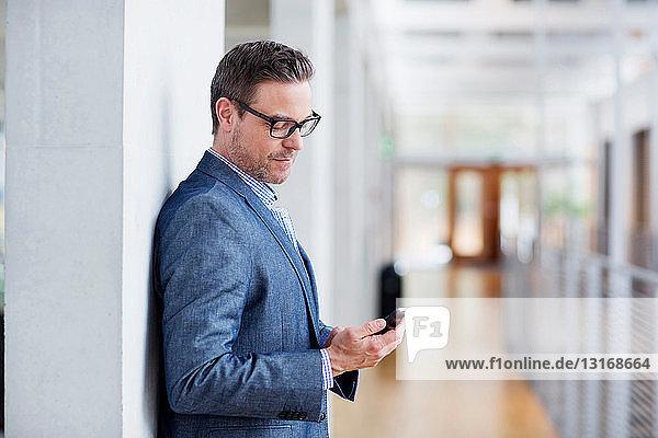 Mann sieht Handy an