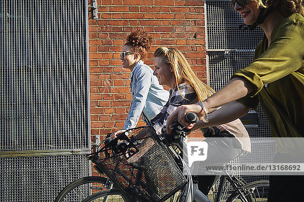 Side view of women cycling on bicycles past warehouse