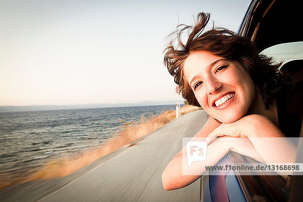 Frau lächelt aus dem Autofenster