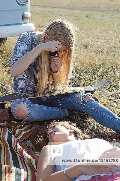 Junge Frau fotografiert Freundin auf Decke liegend