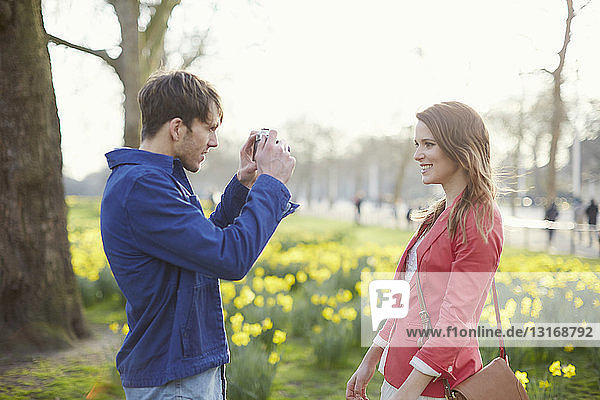 Mid adult man photographing girlfriend in park  London  UK