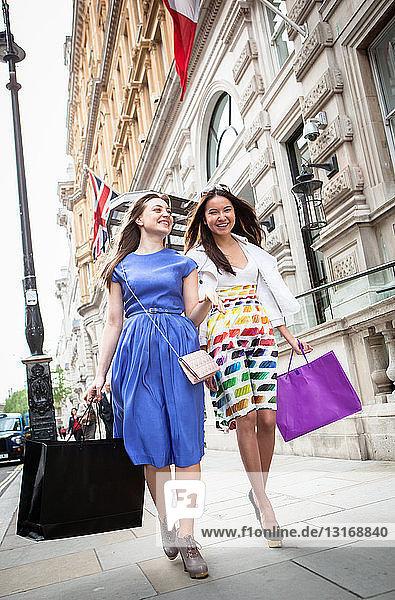 Zwei junge Frauen gehen mit Einkaufstaschen die Londoner Straße entlang