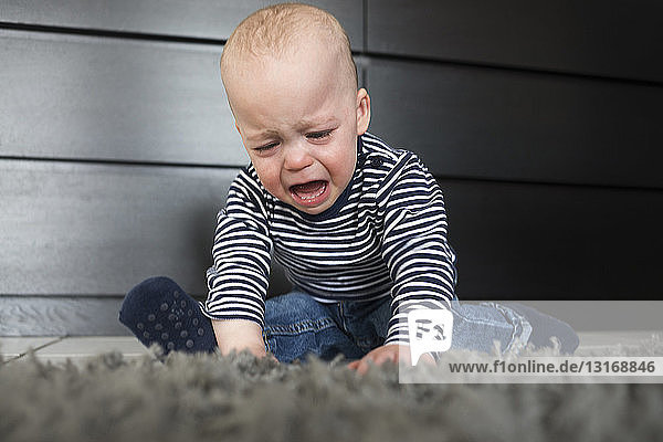 Crying baby boy sitting on rug in living room