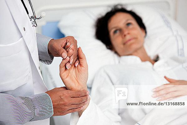 Arzt  der den Puls des Patienten misst