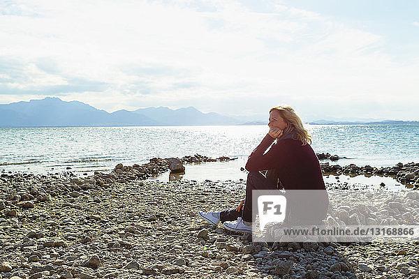 Reife Frau  am See sitzend  nachdenklicher Ausdruck