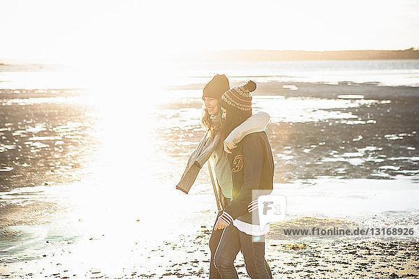 Zwei junge erwachsene Freundinnen spazieren am Strand