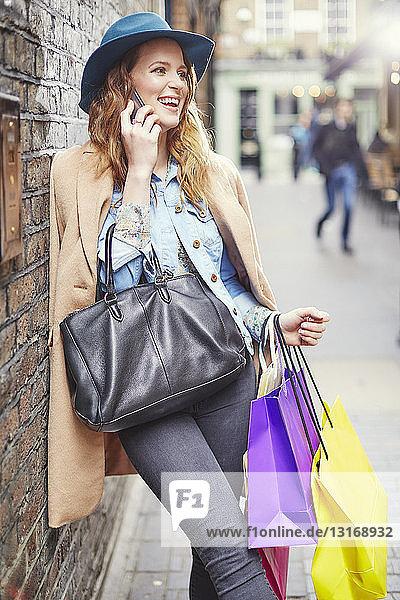 Stylish young woman shopper chatting on smartphone  London  UK