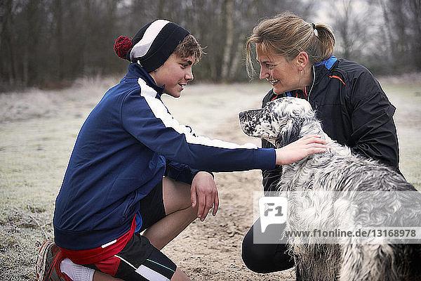 Mutter und Sohn kauern sich hin und streicheln den Hund  von Angesicht zu Angesicht lächelnd