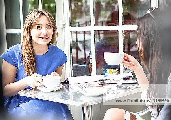 Zwei junge Frauen sitzen vor einem Café und trinken Kaffee