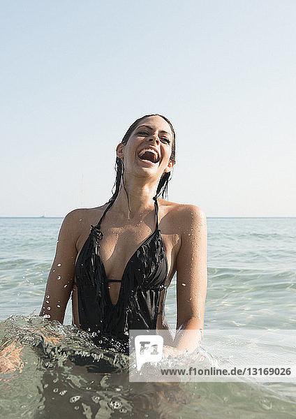 Portrait of young woman wearing bathing costume splashing in sea