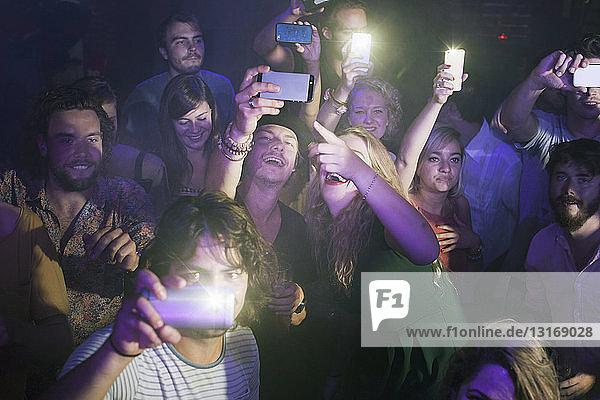 Eine Gruppe von Freunden beobachtet und fotografiert einen Darsteller im Club