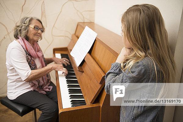Granddaughter watching grandmother playing piano