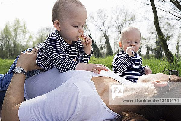 Zwillingsbrüder und Mutter picknicken auf dem Feld