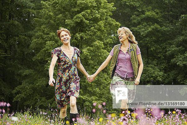 Zwei Frauen halten sich an den Händen und rennen auf einer Wildblumenwiese