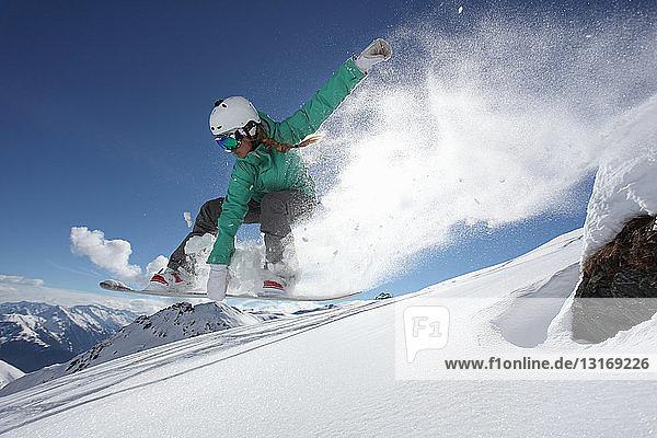 Junge Frau springt auf Snowboard  Mayrhofen  Tirol  Österreich