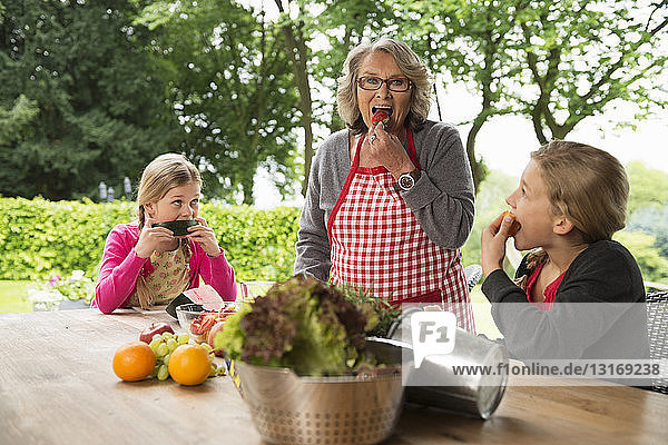 Two sisters and grandmother at patio table eating fresh fruit
