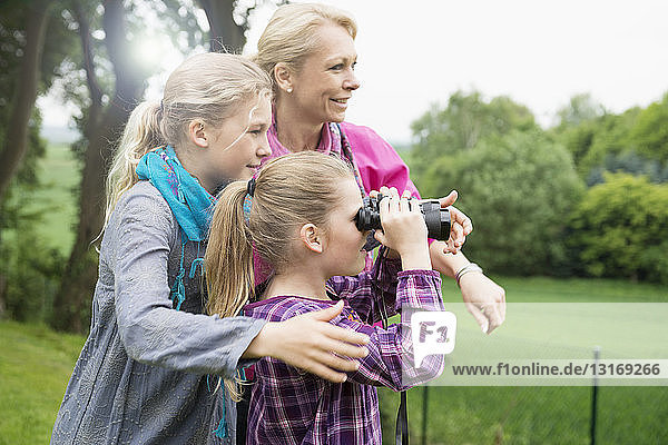 Mother and daughters using binoculars