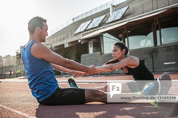 Mann und Frau sitzen auf dem Boden und strecken sich