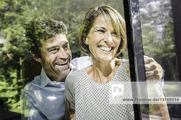 Glückliches reifes Paar schaut durch das Fenster eines neuen Hauses