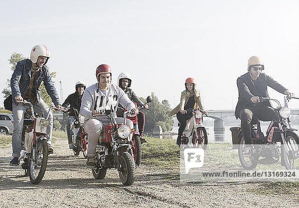 Gruppe von Freunden auf Moped am See