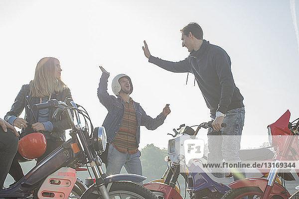 Gruppe von Freunden sitzt auf einem Moped  zwei Männer geben High Five
