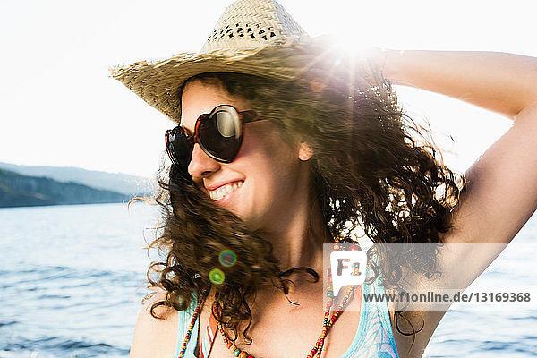 Frau mit Strohhut lächelt am Strand