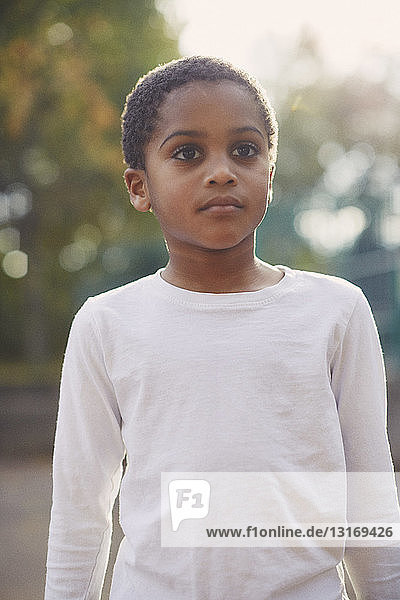 Portrait of elementary schoolboy standing in school playground