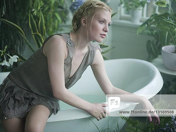 Junge Frau sitzt auf dem Rand einer Badewanne  im Badezimmer voller Pflanzen
