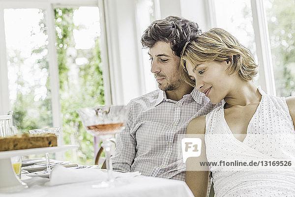 Junges Paar am Esstisch bei einer Party
