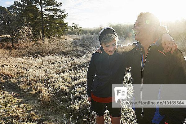 Mutter und Sohn auf der Wiese mit Sportkleidung umarmt und lächelnd